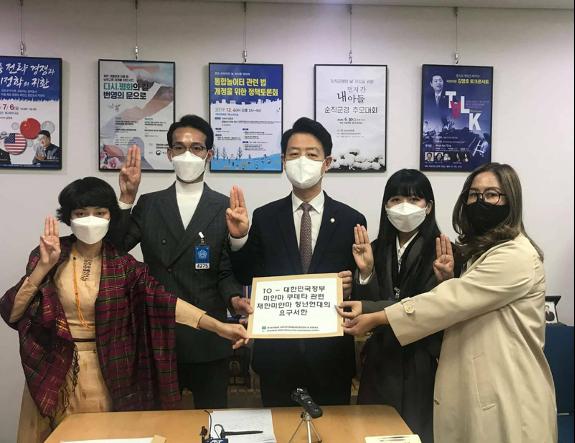 在南韓的緬甸人一直在「國際線」上發聲,讓南韓民眾了解緬甸當地情況。圖為Moe(右二)於3月11日前往韓國國會與議員金映豪(中)會面,眾人在會後舉起象徵反抗極權的「三指禮」。(受訪者提供)