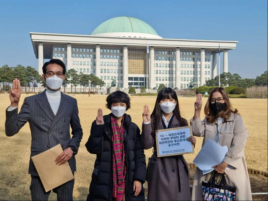 一場政變改變緬甸民眾的生活。Moe(右二)於今年3月11日在南韓國會會見議員前,在場外舉起象徵反抗極權的「三指禮」。(受訪者提供)