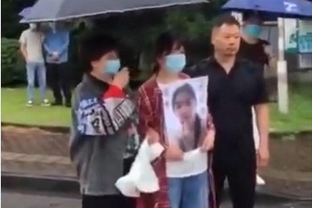 6月19日,寧波工程學院被黑人外教殺害的陳某君家屬手舉遺像,向學校討公道。(視頻截圖)