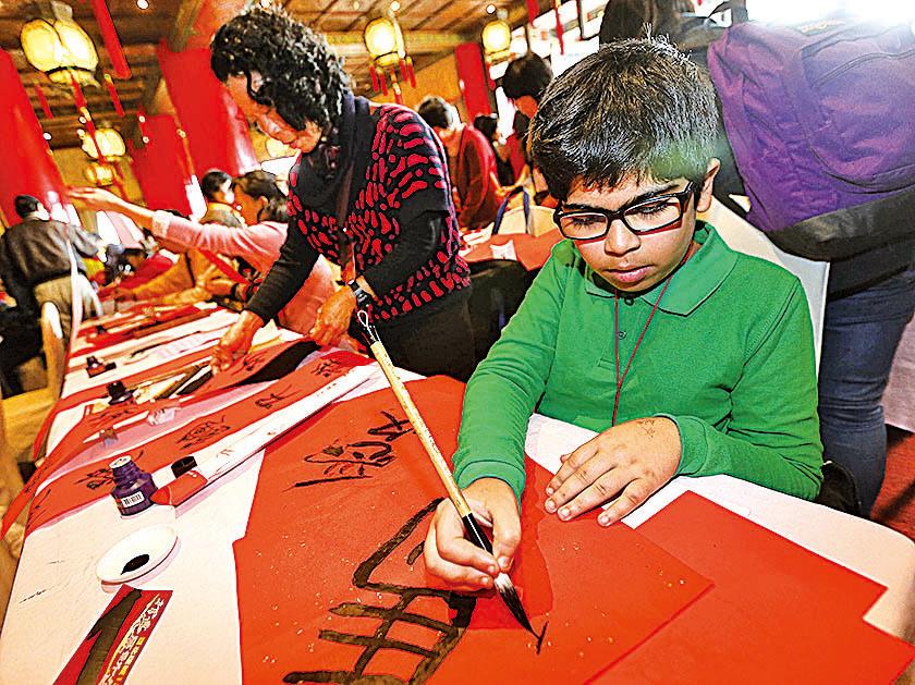 多國研究發現,孩子學正體字有助開發智慧,且越早學智商越高。圖為台灣「第9屆漢字文化節」,民眾揮毫寫下新年願望。(中央社)