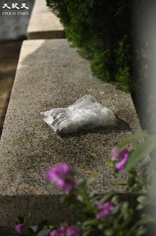 紅衣男子向《蘋果日報》廠房內拋擲的兩袋物品。(言午/大紀元)