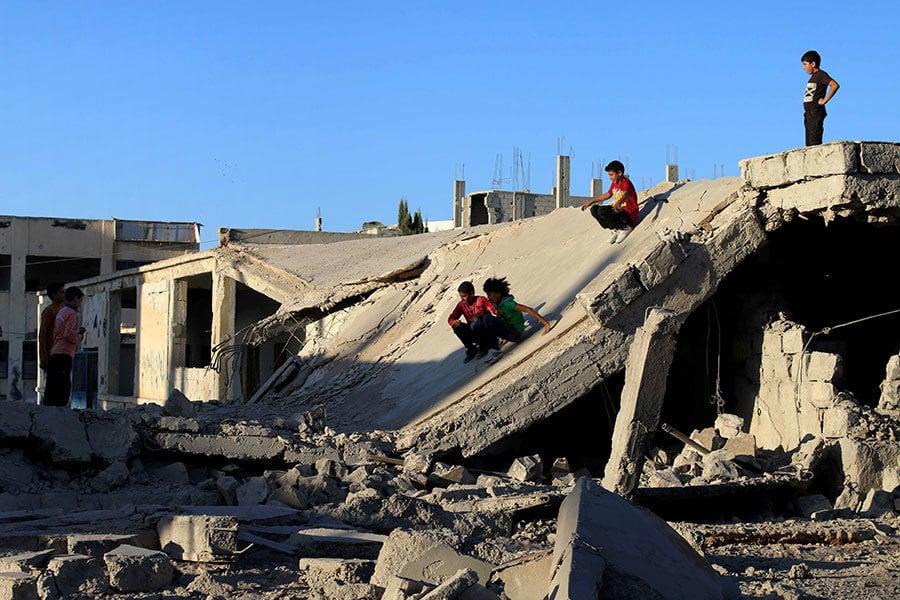美俄10日達成的敘利亞停火協議,於當地時間12日的日落生效。圖為12日數名敘利亞孩童在被戰火廢墟中玩耍。(MOHAMAD ABAZEED/AFP/Getty Images)