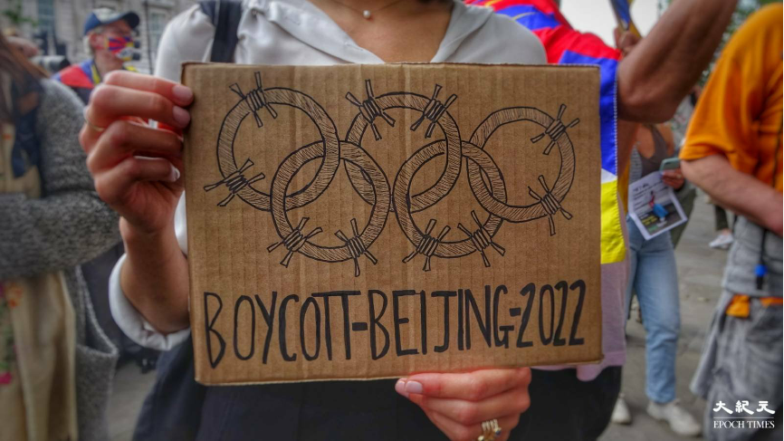 參與集會人士舉起杯葛2022年北京冬季奧運會的自製標語,並在五環上加上鐵絲網圈,諷刺中共打壓人權。(文苳晴/大紀元)