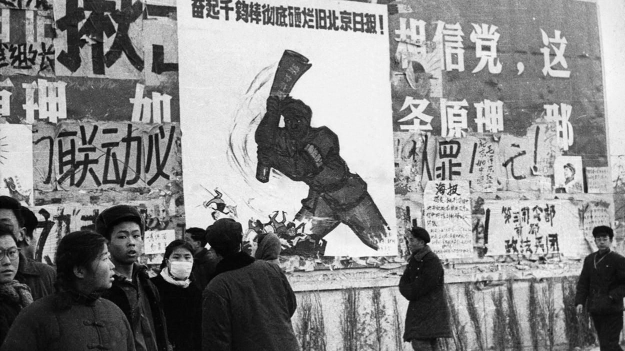 中共從7月起,將開展為期2年的計劃經濟最後殘體的「供銷社」的試點工作。圖為毛時代一群中國青年走過標語牌。(JEAN VINCENT/AFP/Getty Images)