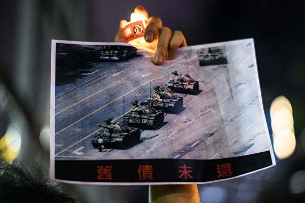 圖為2020年6月4日,一名香港人在維多利亞公園燭光悼念在1989年六四中被中共殺害的學生和市民。他拿著的海報展示的是著名的被稱為「坦克人」的男子在北京長安街上隻身阻擋中共坦克車隊前進。(ANTHONY WALLACE/AFP via Getty Images)