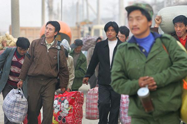 2021年5月,新的數據顯示,中國的大城市對農民工的吸引力正在減弱,許多農民工不再嚮往到大城市打工。圖為2005年10月26日中國的幾名農民工在趕路。(FREDERIC J.BROWN/AFP via Getty Images)