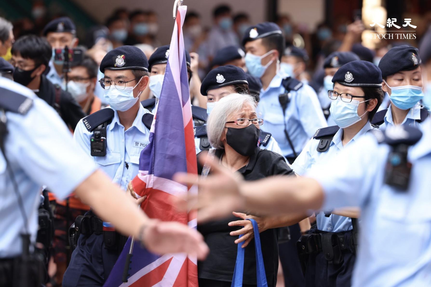 7月1日午後2時40分許,王婆婆手持英國旗幟出現在達百德新街及記利佐治街交界處,之後被數十警員包圍後被帶走。(李辰/大紀元)