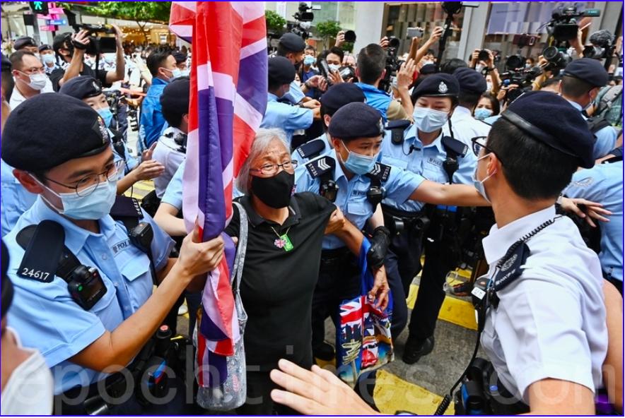 7月1日午後2時40分許,王婆婆手持英國旗幟出現在達百德新街及記利佐治街交界處,之後被數十警員包圍後被帶走。(宋碧龍/大紀元)