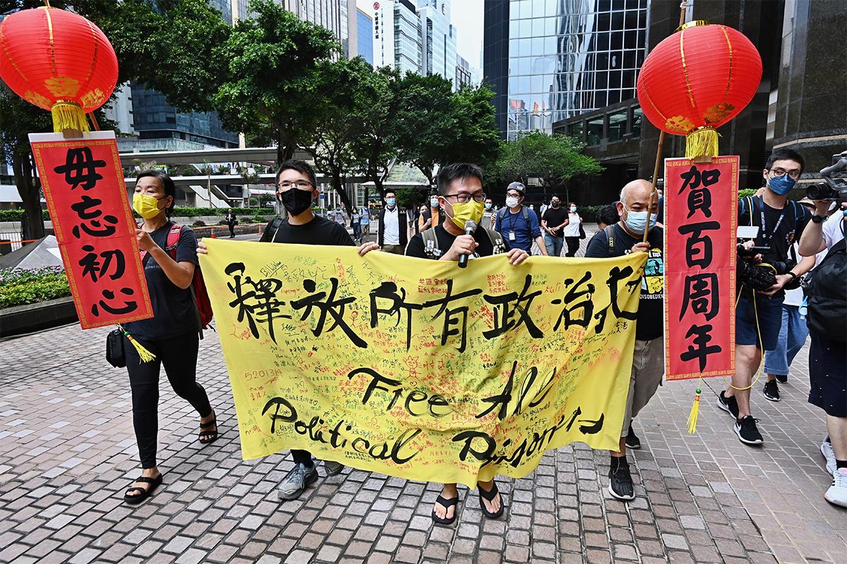 4名社民連成員,昨日從灣仔家計會前遊行到金紫荊廣場附近的香港萬麗海景酒店外,要求釋放政治犯、實現普選。(宋碧龍/大紀元)