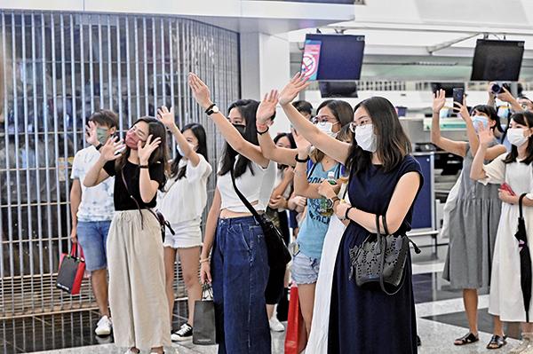 在機場離境大堂,送機的市民揮手告別親朋好友。(宋碧龍/大紀元)