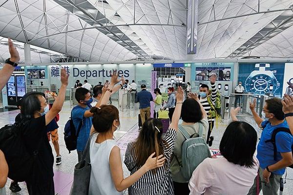 6月30日,在香港機場離境大堂,出現一幕又一幕揮手告別移民親友的畫面。(宋碧龍/大紀元)