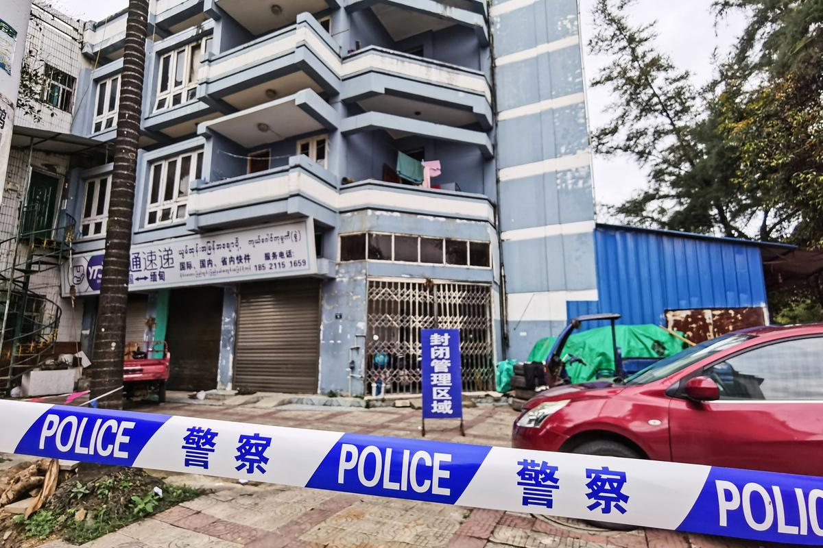 雲南瑞麗再現疫情,並且瑞麗市姐告國門社區調整為高風險地區。圖為2021年7月5日警察拉起封鎖帶封鎖社區。(STR/AFP via Getty Images)