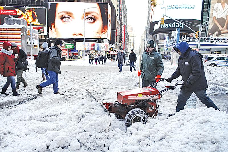 陽光露臉了,美國民眾開始鏟雪。紐約市時代廣場。(AFP)