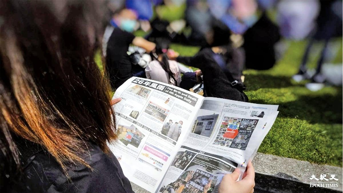 80後香港女子Joyce曾因參與「國際線」宣傳工作,在去年8月10日大搜捕後,決定連同丈夫帶父母前往英國。圖為6月27日當日,集會人士閱讀蘋果號外的情況。(文苳晴/大紀元)