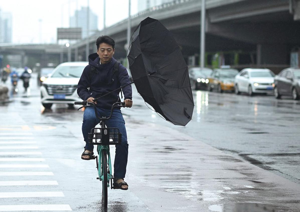 2021年7月12日,在北京的一條街道上,一名男子在蹬車時雨傘被風吹反。(NOEL CELIS/AFP via Getty Images)