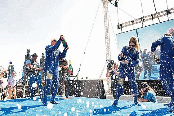 布蘭森在完成太空旅行後,和其他太空旅行者一起進行慶祝。(PATRICK T. FALLON/AFP via Getty Images)