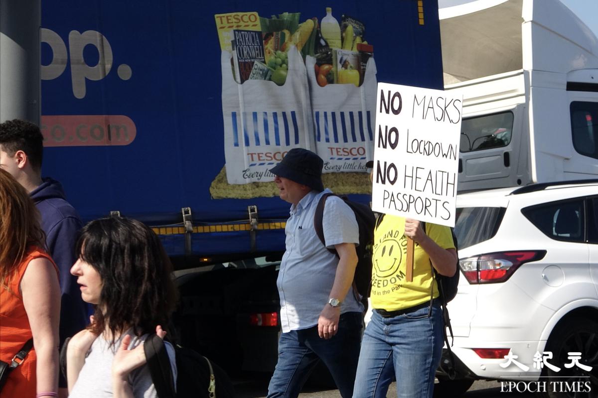 Chris(黃衣者)接受本報採訪時表示,反對封城和疫苗護照。(文苳晴/大紀元)