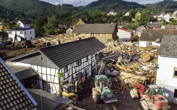 7月17日,在德國舒爾德,救援人員和居民用電鏟和拖拉機清除房屋前的廢墟、樹木、傢俬和汽車。(Getty Images)