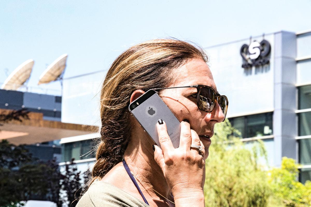 2016年8月28日,一名打電話的女士走過以色列公司NSO集團的門前。(AFP)