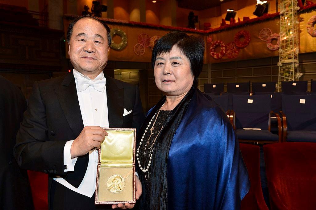 2012 年 12 月 10 日,諾貝爾文學獎得主莫言(左)與夫人杜茵蘭在斯德哥爾摩音樂廳舉行諾貝爾獎頒獎典禮後展示獲獎作品。(JONAS EKSTROMER/AFP via Getty Images)