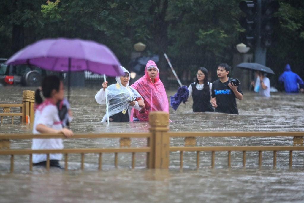 網絡社交媒體上有影片顯示,7月20日下午,鄭州在4小時之內就被洪水淹沒。有水利專家表示,中國不存在任何自然的洪水,洪水都是人為控制。中共官媒消息顯示,中共官方在給水庫洩洪整整12小時後才發佈洩洪公告。圖爲7月20日,鄭州市民涉水而行。(STR/AFP via Getty Images)