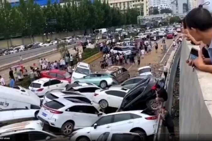 7月22日,鄭州洪水漸漸退去後,在京廣隧道出入口處逾百輛車露出了水面。(影片截圖)