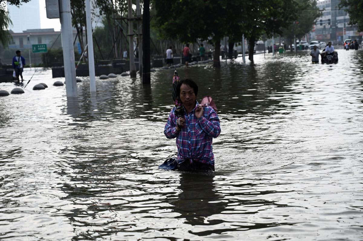 中國河南7月17日以來多地暴雨成災,圖為一名男子在新鄉市街頭涉水行走,攝於2021年7月23日。(Jade Gao/AFP/Getty Images)