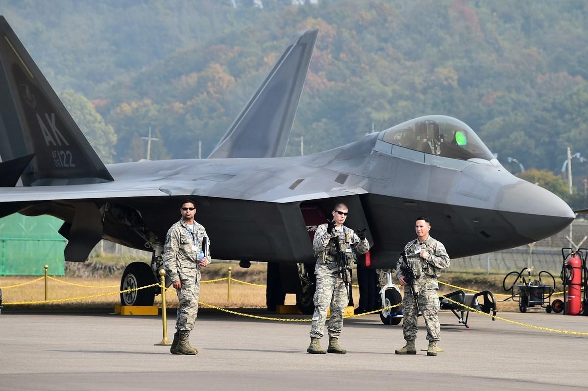 7月以來,美軍在太平洋海域接連多場大規模軍演。英國要在亞洲海域永久部署2艘軍艦,將形成美英日亞太圍堵中共態勢。圖為美國士兵在停機坪F-22猛禽戰鬥機前站崗。(JUNG YEON-JE/AFP via Getty Images)