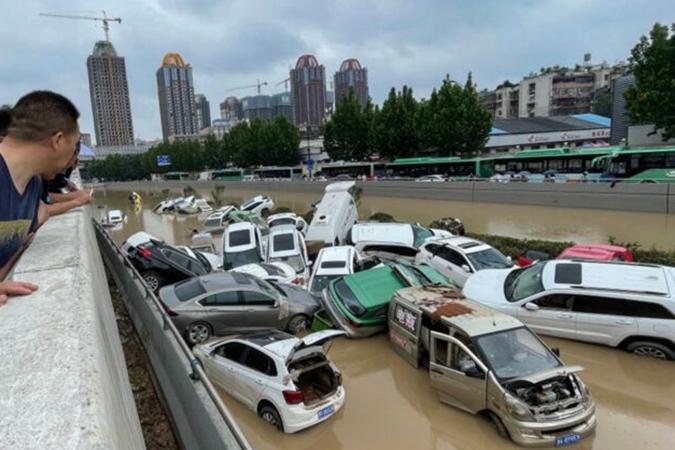 7月21日,民眾在鄭州京廣路隧道外圍觀被淹沒的汽車。(STR/AFP via Getty Images)