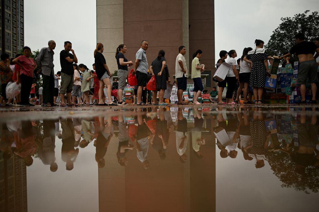 作為一家落敗的企業,鴻星爾克日前向河南災區捐贈5,000萬元物質。圖為正在排隊領取救援物資的鄭州市民。(NOEL CELIS/AFP via Getty Images)