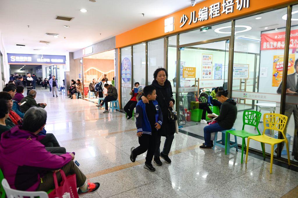 中共當局目前正對校外輔導行業進行嚴厲打擊,官方在7月24日正式發佈的一份文件,幾乎將中國的校外培訓機構資本市場徹底關閉。圖為北京一家兒童電腦培訓中心外的家長和學生。(WANG ZHAO/AFP via Getty Images)