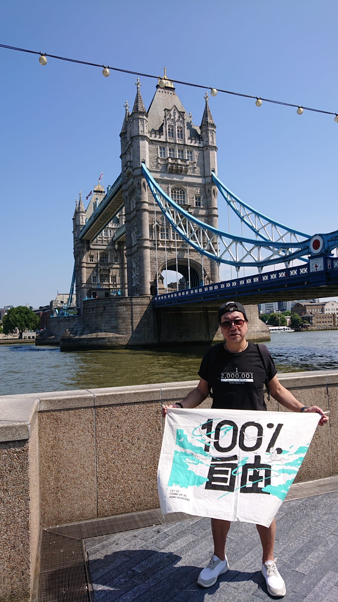 手持「100% 自由 、Let Us Stand Up As Hong Kongers」攝影於倫敦橋底。(受訪者提供)
