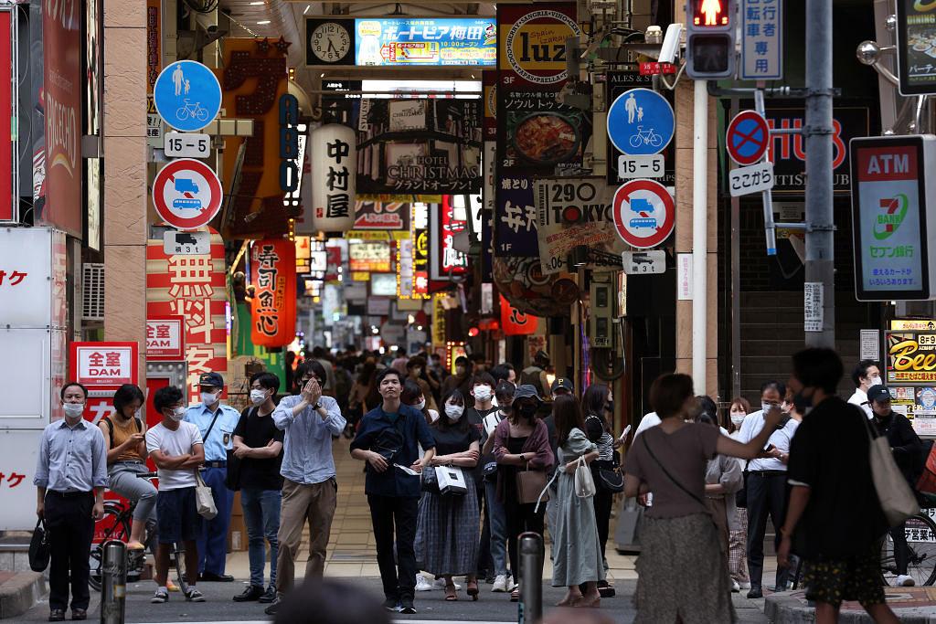 8月2日,在日本大阪,人們戴著防護口罩,在梅田區的夾道中等待過馬路。(Getty Images)