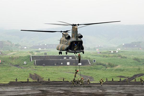 日本計劃在距離台灣300公里的石垣島增加部署導彈部隊以威懾中共。前美國高官蓬佩奧與博明都呼籲美國政府嚴肅對待中共武統台灣的威脅。圖為在日本東富士實彈演習的自衛隊士兵用繩索自CH-47J直升機垂降。(Akio Kon - Pool/Getty Images)