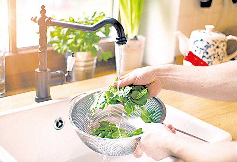 使用可以過濾水流的容器清洗香草。