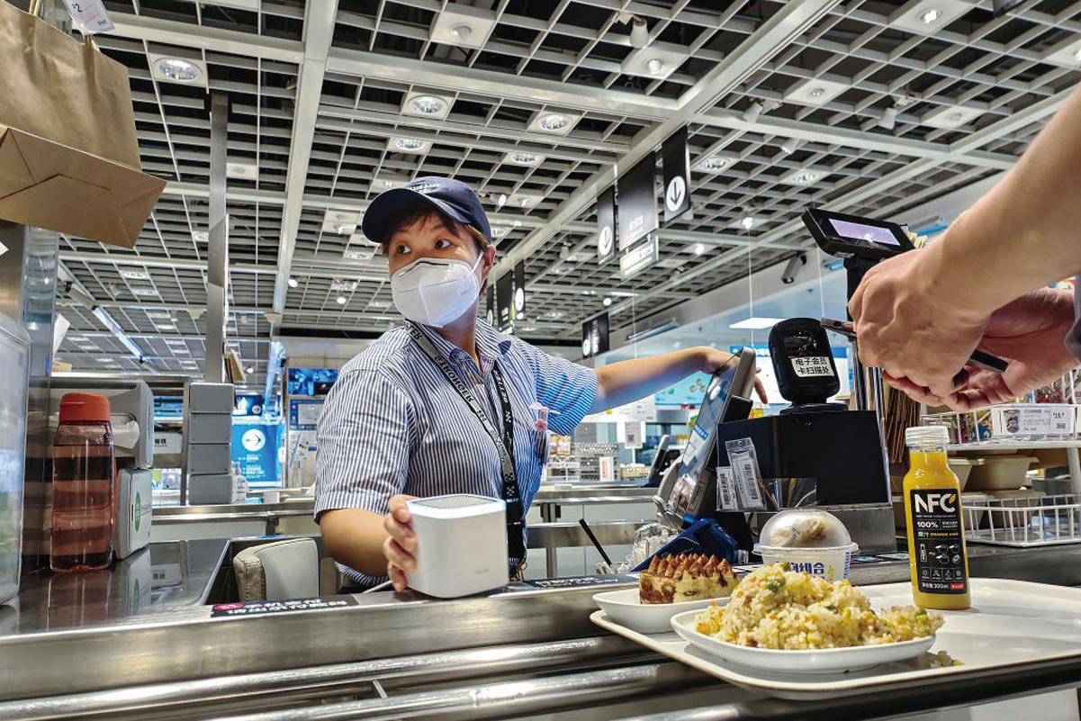 8月11日,在武漢市LIVAT購物中心的一家餐廳,一名收銀員戴著口罩為顧客結賬。(Getty Images)