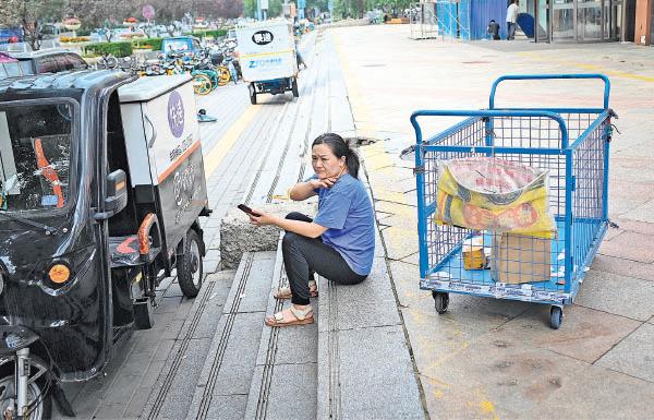 7月15日,北京一家商場外正在休息的送貨員。(Getty Images)