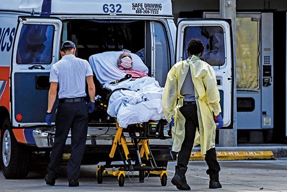 8月16日,邁阿密的醫務人員從救護車上用擔架轉移一名確診患者。(Getty Images)