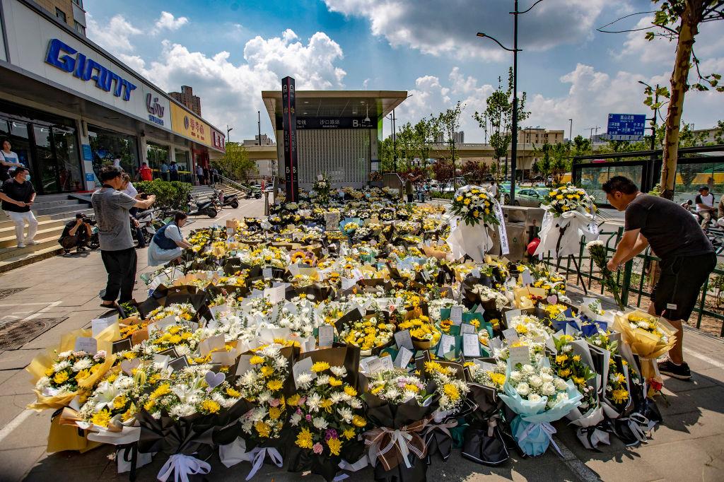 今年7月27日,鄭州地鐵站前,民眾為悼念在洪水中逝去的親友獻花。(STR/AFP via Getty Images)