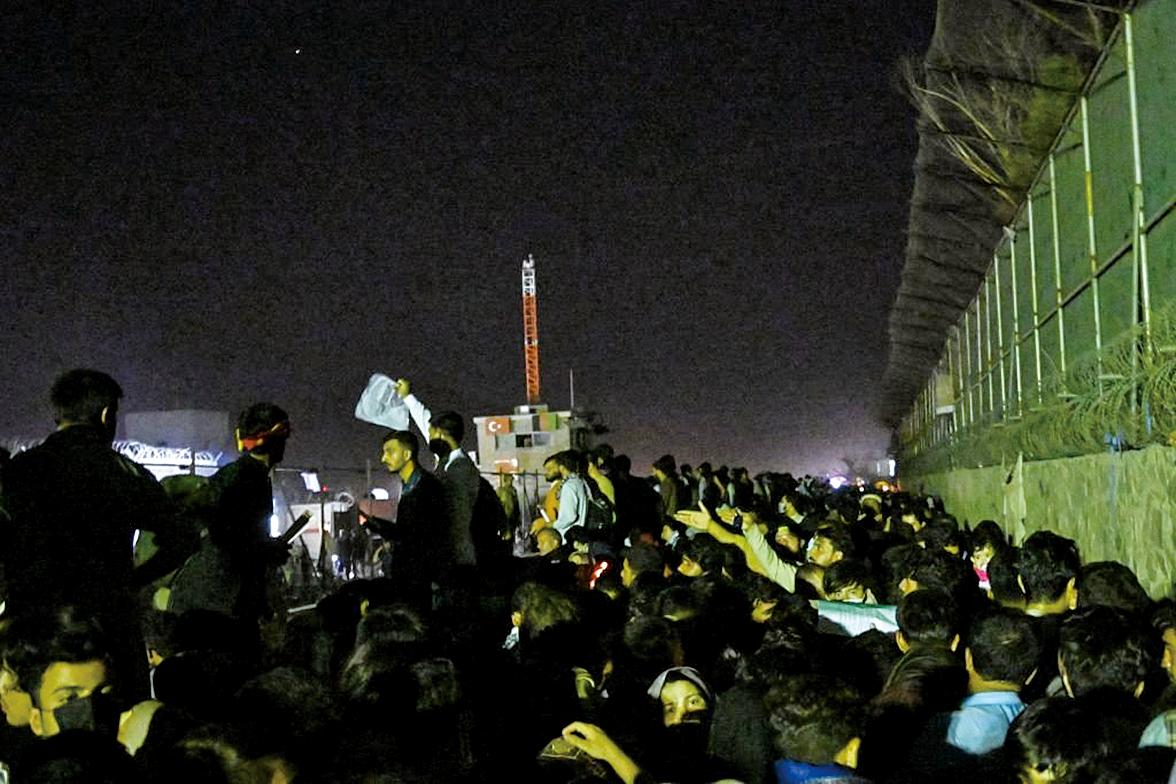 2021年8月22日深夜,阿富汗人聚集在喀布爾國際機場外等待,希望能夠搭乘飛機離開該國。(WAKIL KOHSAR/AFP via Getty Images)