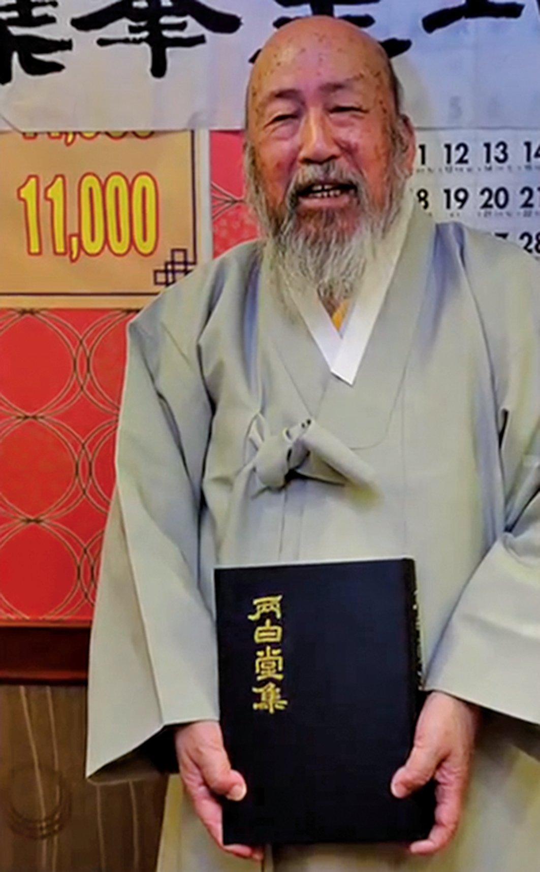 韓國95歲高齡的文相鎬手持著他首部出版的漢詩詩集《兩白堂集》。(未解之謎影片截圖)