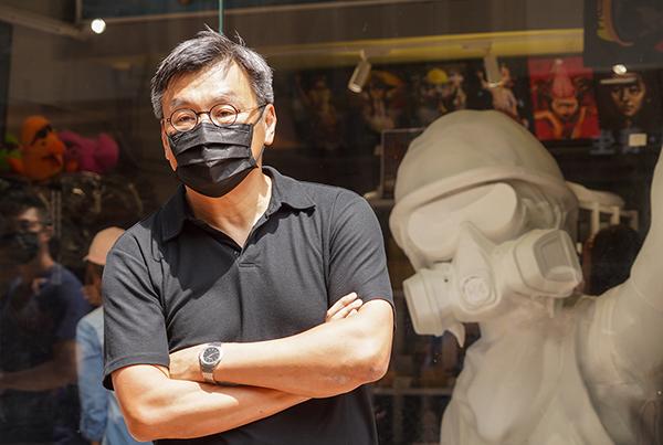 周小龍說,他的理念是「白色恐怖,當佢無到」。圖為Chickeeduck藝術生活百貨荃灣店5月6日遭警方國安處搜查後,周小龍在店鋪陳設的香港民主女神像前。(大紀元資料圖片)