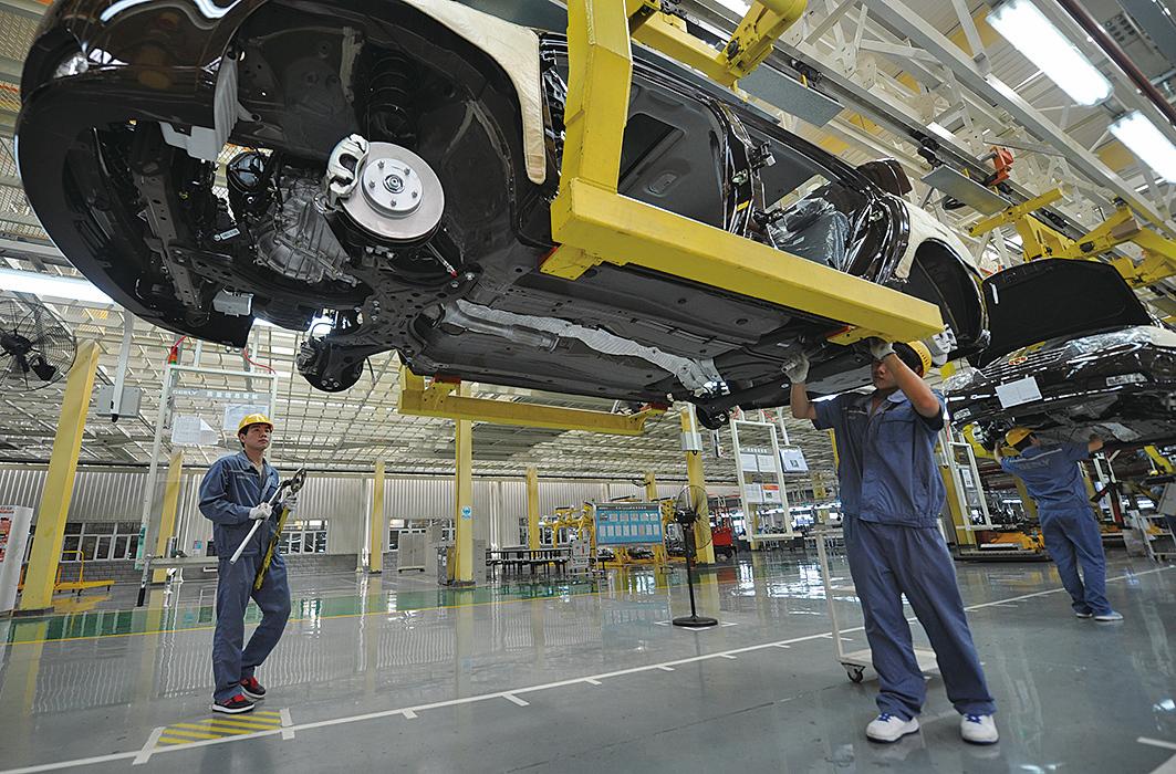 圖為在汽車生產線工作的工人。(AFP)