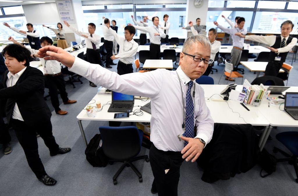 久坐往往導致人體血糖水平、膽固醇升高。日本是人均最長壽的國家,企業鼓厲員工於工作期間定時進行舒展活動。( TORU YAMANAKA/AFP via Getty Images))