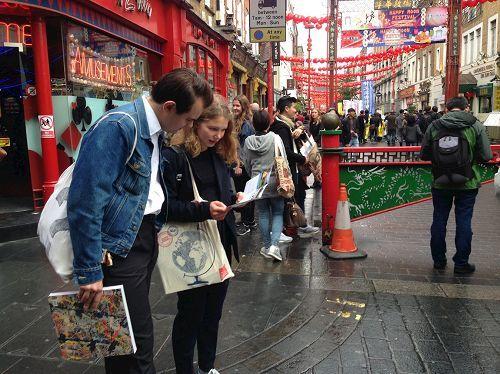 2016年10月1日下午,在倫敦唐人街,法輪功學員的反迫害遊行隊伍經過後,一對年輕人在非常專注地閱讀真相傳單。