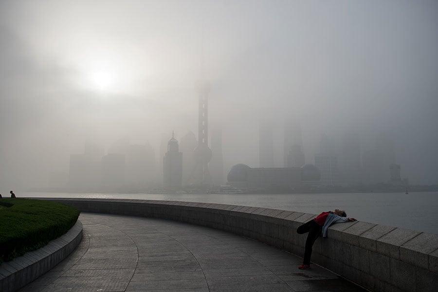 上海官媒近日發文聲稱再多的「風言風語」也不能讓其改變房地產政策方向。圖為霧霾中的上海。(JOHANNES EISELE/AFP/Getty Images)