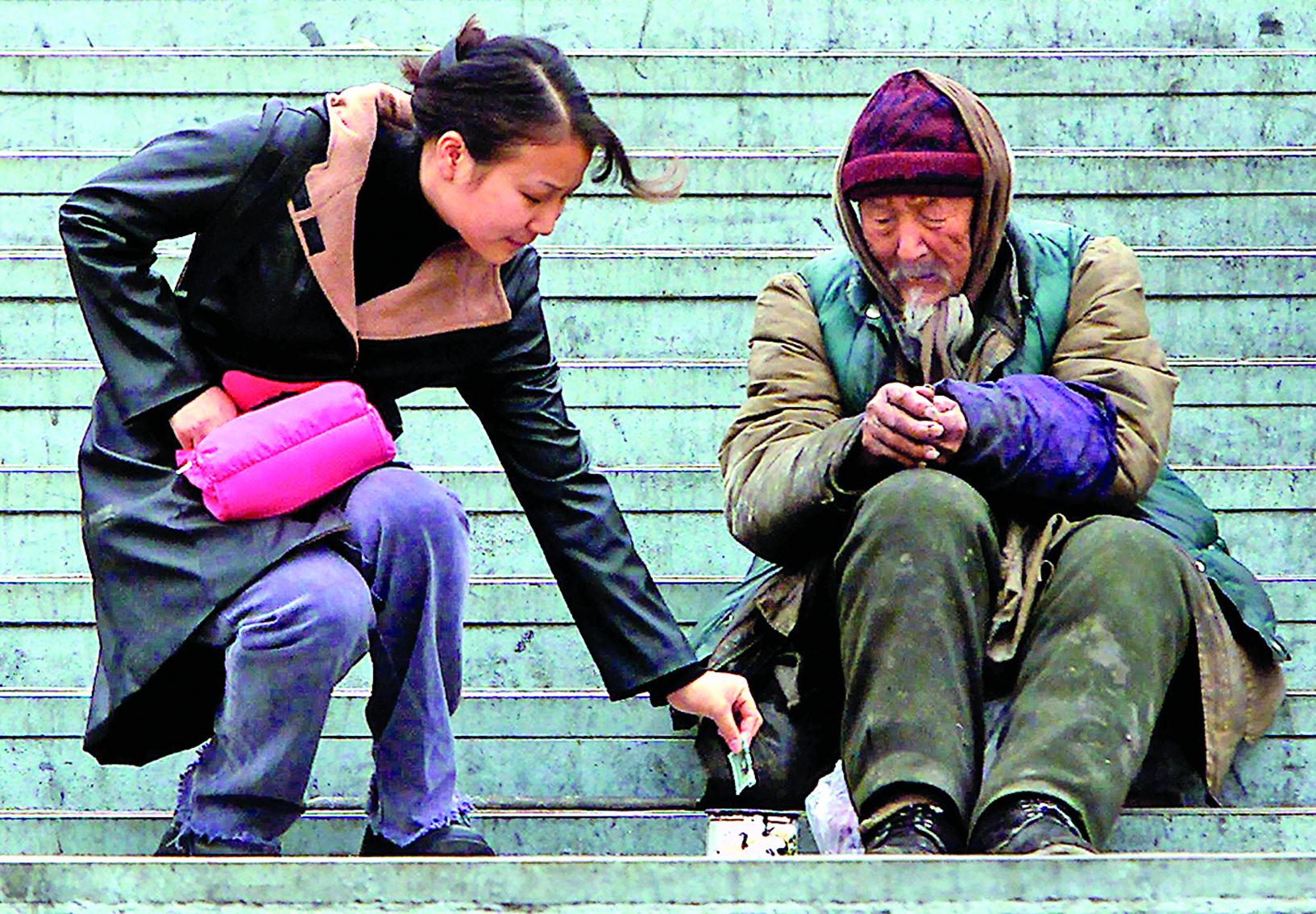 中共官方一家研究機構的報告稱,每天有約1,370老人失蹤。圖為北京街頭,一女子給無家可歸的乞討老人零錢。(AFP)