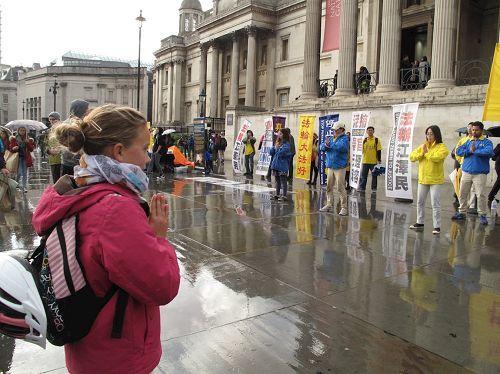 2016年10月1日下午,倫敦小女孩克勞伊(Chloe)在特拉法加廣場(Trafalgar Sqare)認真模仿學煉法輪功功法。