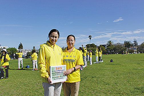 法輪功學員沈越千和王少華在三藩市教會區多洛瑞斯公園參與呼籲制止活摘小型遊行、徵簽活動。(張小清/大紀元)