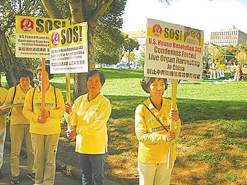 法輪功學員羅慕欒(中)和米瑞京(右)在三藩市教會區杜伯斯公園參與呼籲制止活摘小型遊行、徵簽活動。(張小清/大紀元)